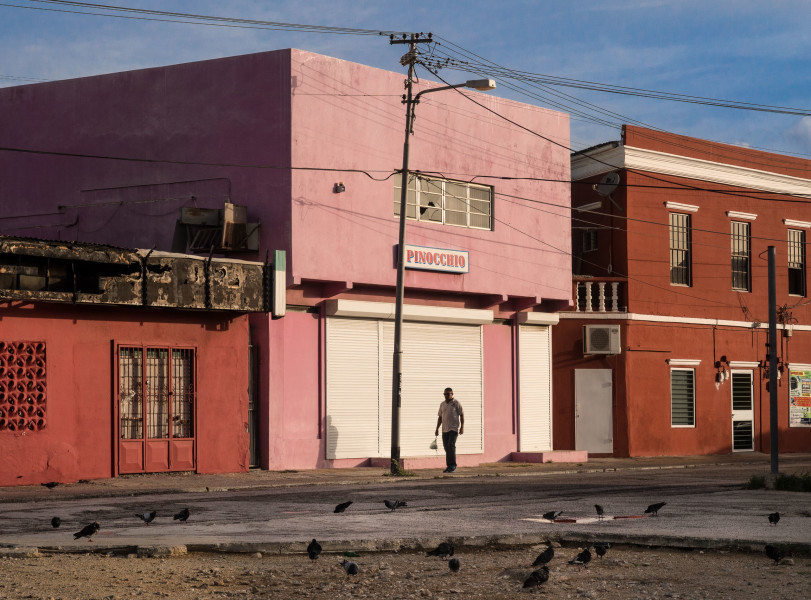 Ben Asen Personal Work Photo: Color photo of a man walking down a street in Aruba in front of a building with a sign that reads Pinocchio