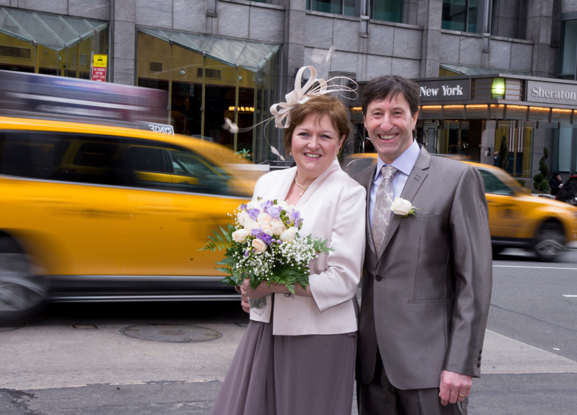 Ben Asen Celebration Photo: Bride and groom in New York City with taxis and New York sign in the background