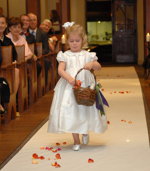 Ben Asen Celebrations Photo: Flower girl at wedding in a church throwing flower petals down the aisle