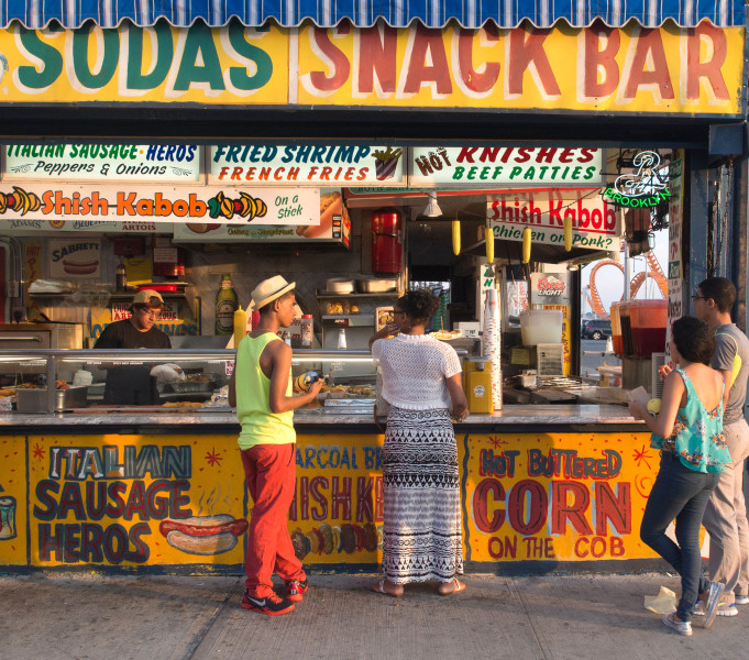 Ben Asen Personal Work Photo: Color photo of snack bar in Coney Island, Broolyn, New York with man with brimmed straw hat and 3 other people.