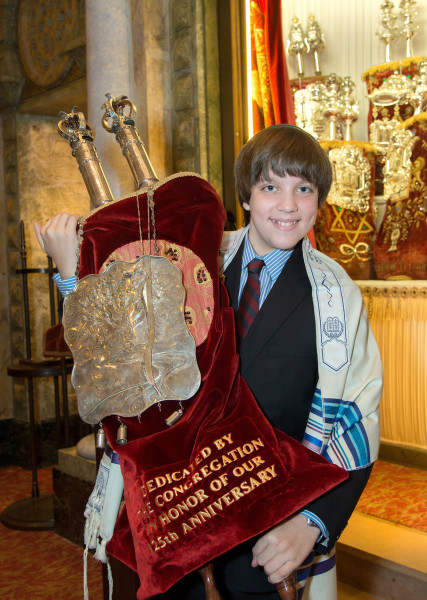 Ben Asen Celebration Photo: Bar Mitzvah boy holding the Torah in a synagogue
