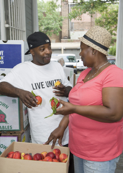Ben Asen Editorial Photo: Man and woman working at a food distribution event for United Way of NYC in Brooklyn New York