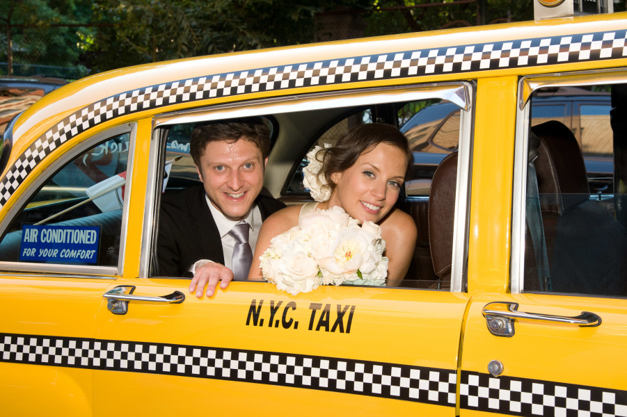 Ben Asen Celebrations Photo: Color photo of bride and groom looking out the window of a New York City taxi