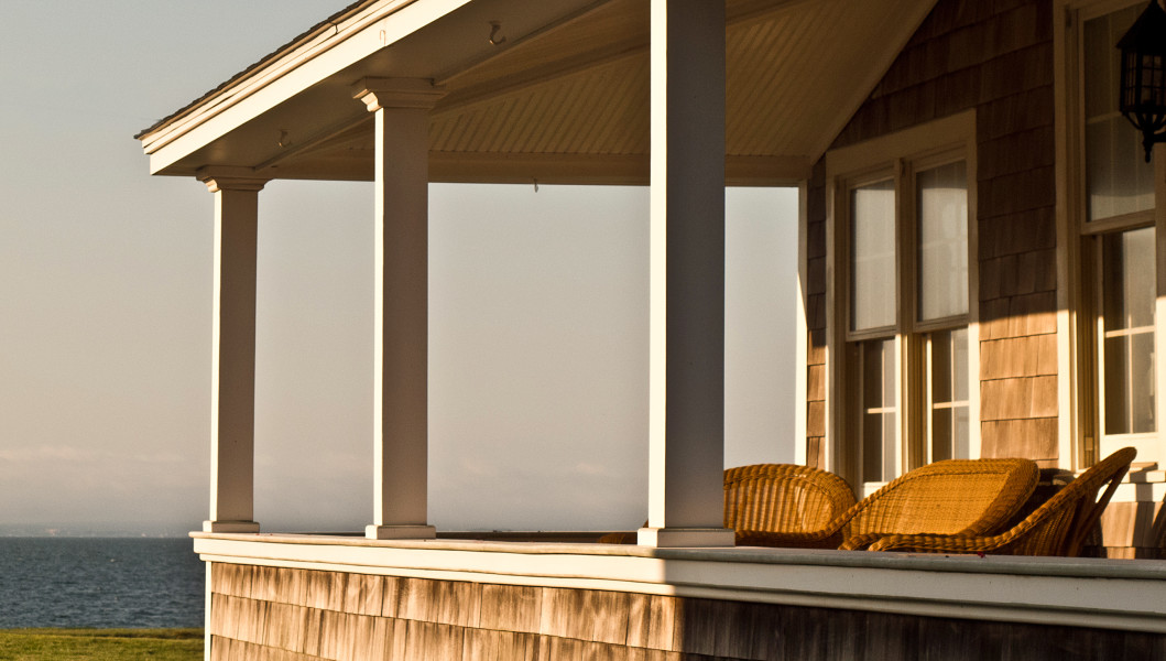 Ben Asen Personal Work Photo: Color photo of a house porch with wicker chairs at sunrise on Cape Code in Falmouth Massachusetts.