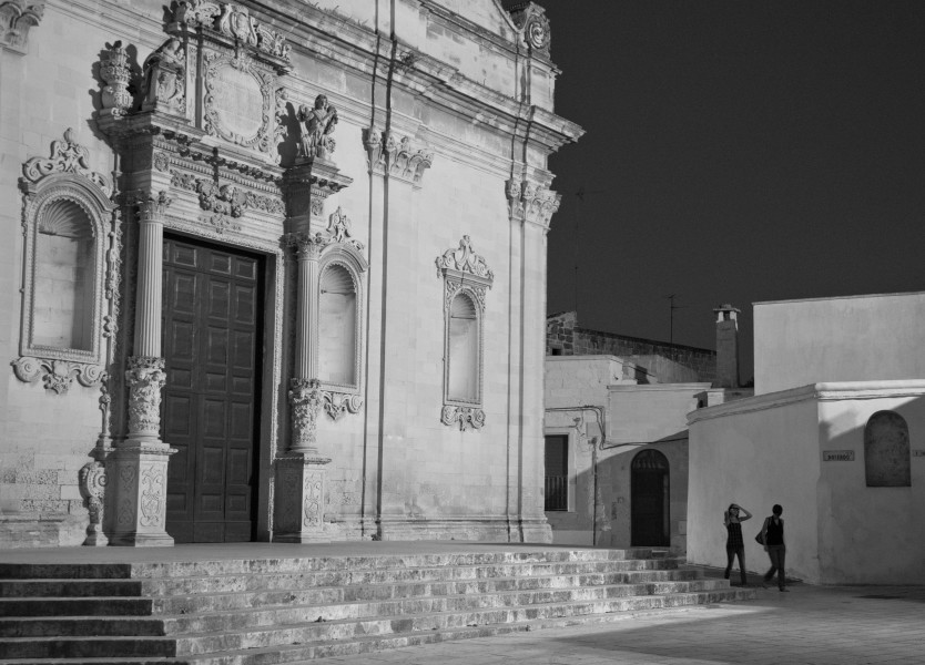 Ben Asen Personal Work Photo: Black and white photo of 2 woman walking at night past church in Muro Leccese in the Puglia region of Italy.