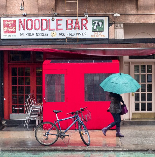 Ben Asen Personal Work Photo: color photo of a woman with an umbrella walking past the Noodle Bar in Greenwich Village, New York City