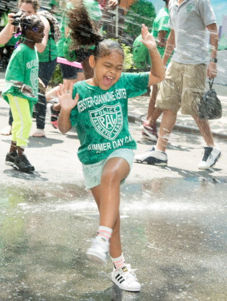 Ben Asen Editorial Photo: Police Athletic League (PAL) of NYC, young PAL girl under a fire hydrant sprinker at PAL summer event