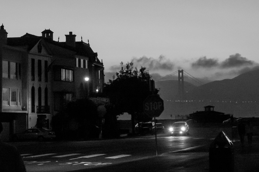 Ben Asen Personal Work Photo: Black and white photo of a street at night with oncoming car with lights with the Golden Gate Bridge in the background.